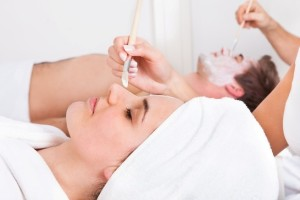 Therapist Applying Facial Mask To Young Couple At Beauty Salon